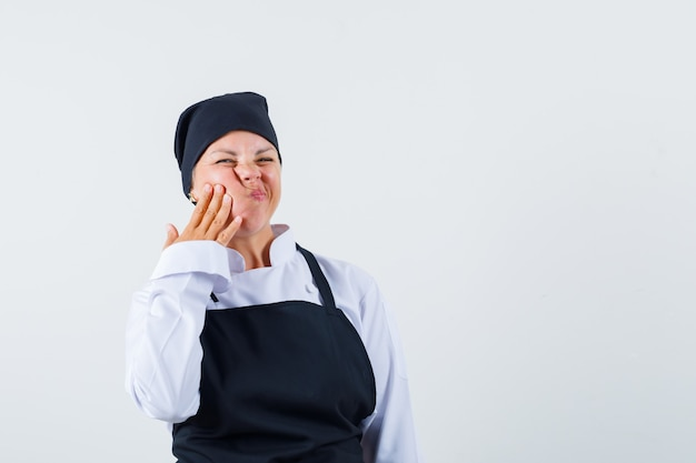 Female cook in uniform, apron suffering from toothache and looking uncomfortable , front view.
