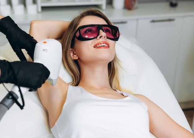 Косметолог-женщина в униформе использует машину для лазерной эпиляции в комнате с клиентом, лежащим на медицинском столе в клинике красоты.