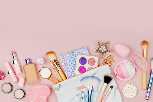 ピンクの背景に口紅のブラシやその他のアクセサリーと女性の化粧品のコラージュ
