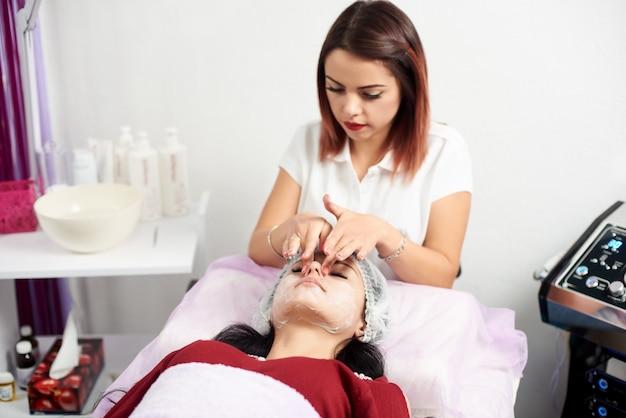 얼굴 마스크를 적용하는 여성 미용사