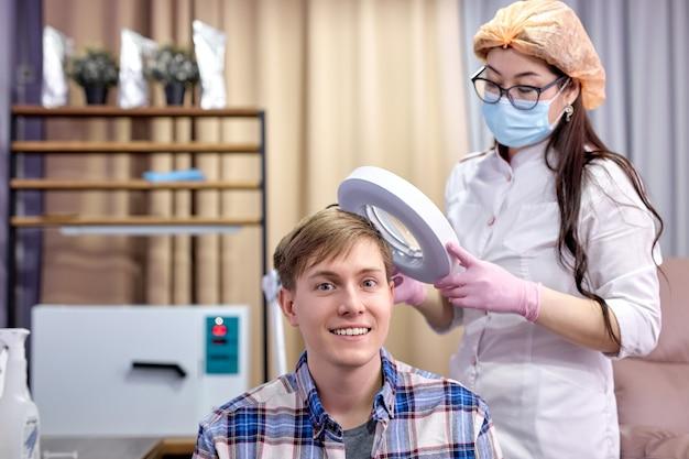 Женский косметолог исследует кожу головы улыбающегося пациента мужского пола с помощью специального дерматологического оборудования, концепции потери волос и трихологии. в ярком современном кабинете