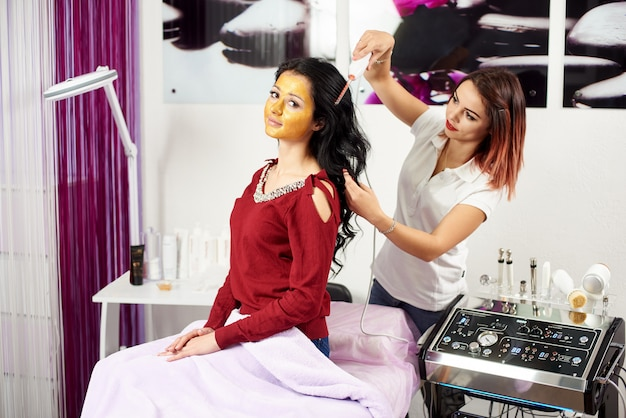Female cosmetologist is giving hair treatment to a brunette client with a gold mask on her face in a modern beauty salon.