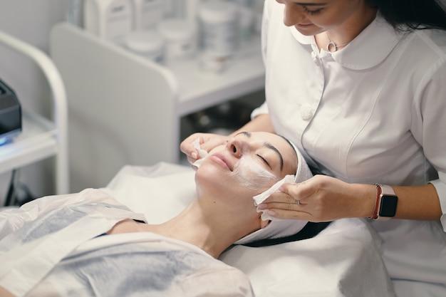 Женский косметолог делает уход за лицом к красивой женщине