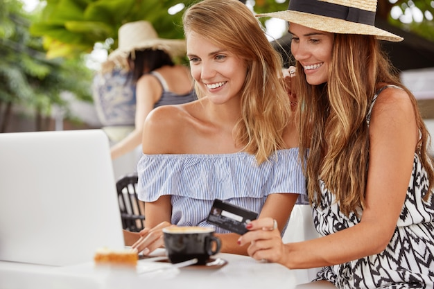Female couple in love make shopping online, rejoice new purchases, have happy looks in laptop computer. online payment or e commerce
