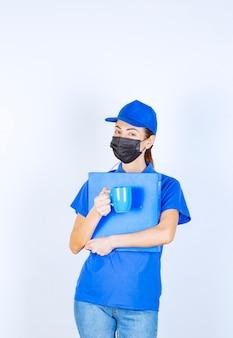 Corriere femminile in uniforme blu e maschera nera che tiene una cartella blu e una tazza di tè.