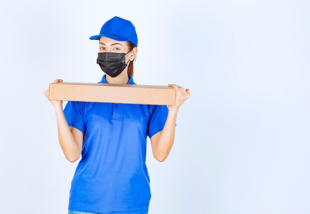 Female courier in blue uniform and face mask delivering a cardboard box to the customer.