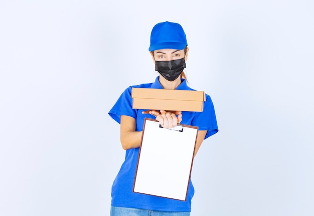 Corriere femminile in uniforme blu e maschera facciale che consegna un pacco di cartone e chiede al cliente di firmare sul bianco.