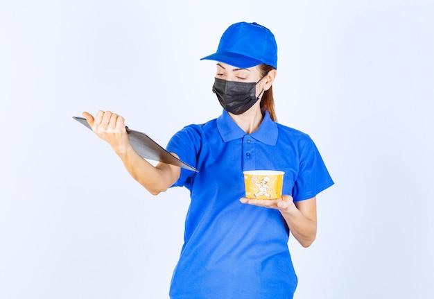Corriere femminile in uniforme blu e maschera facciale che consegna un cibo da asporto e controlla l'indirizzo dall'elenco dei clienti.