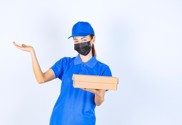 Female courier in blue uniform and face mask holding a cardboard box and pointing to somewhere.