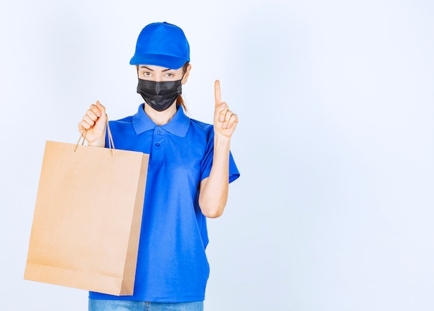 Female courier in blue uniform and face mask holding a cardboard shopping bag and has an idea or thinking.