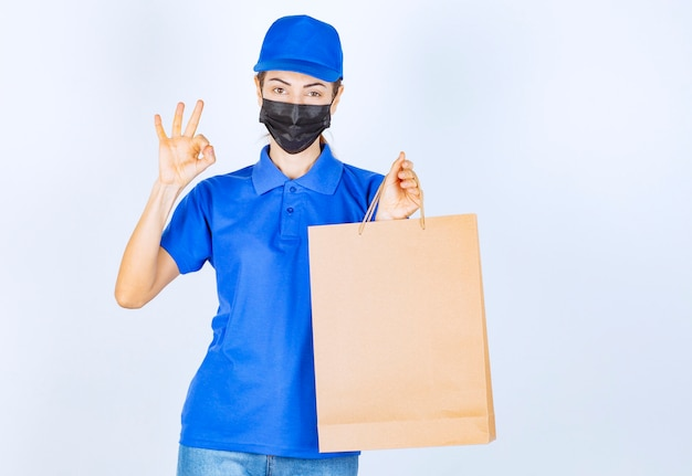 Female courier in blue uniform and face mask holding a cardboard shopping bag and showing satisfaction sign.