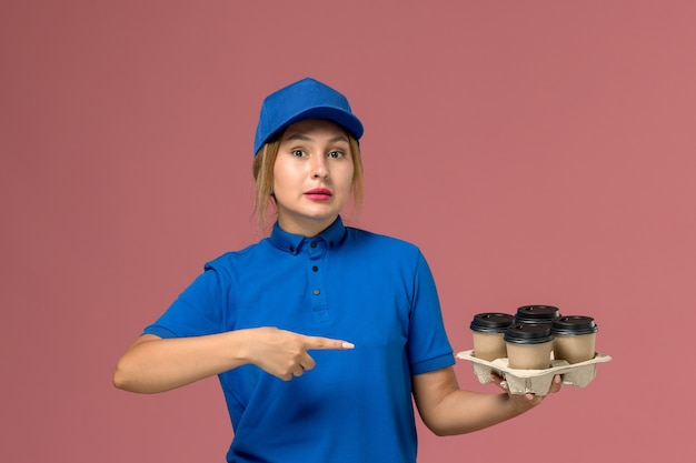 Female courier in blue uniform holding brown delivery cups of coffee pointing out on pink, service uniform delivery job worker