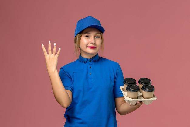 Corriere femminile in uniforme blu che tiene le tazze di consegna marrone di caffè che mostra il numero quattro sul rosa, lavoratore di lavoro di consegna uniforme di servizio