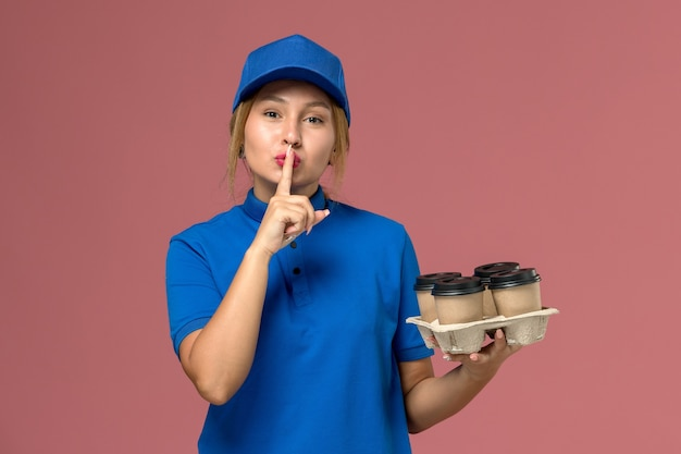Female courier in blue uniform holding brown delivery cups of coffee showing silence sign on pink, service worker uniform delivery