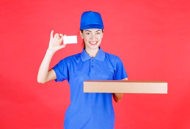 Corriere femminile in uniforme blu che tiene una scatola di cartone e presenta il suo biglietto da visita.