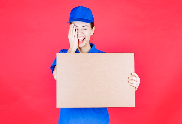 Female courier in blue uniform holding a cardboard takeaway pizza box and covering one eye with hand.