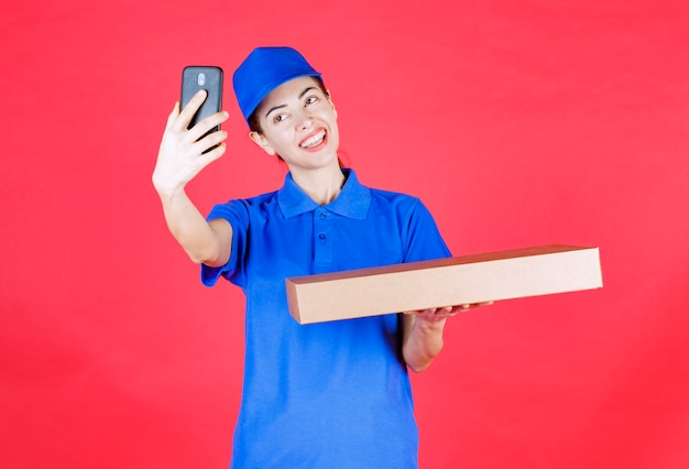 Female courier in blue uniform holding a cardboard takeaway pizza box and taking her selfie.