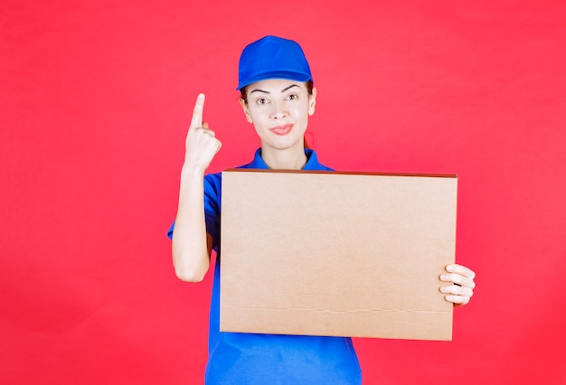 Female courier in blue uniform holding a cardboard takeaway pizza box and thinking or looking confused.