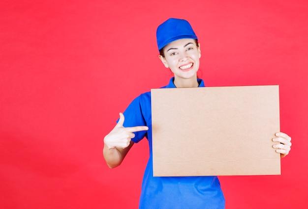 Corriere femminile in uniforme blu che tiene in mano una scatola di cartone per pizza da asporto.
