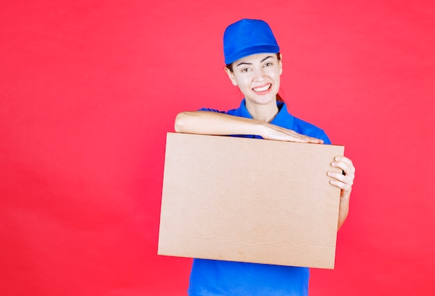 Female courier in blue uniform holding a cardboard takeaway pizza box.