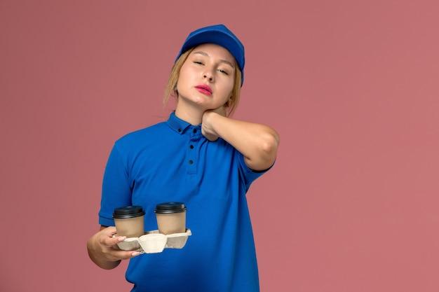 Corriere femminile in uniforme blu che tiene tazze di caffè con mal di collo in rosa, lavoro di consegna uniforme di servizio Foto Gratuite