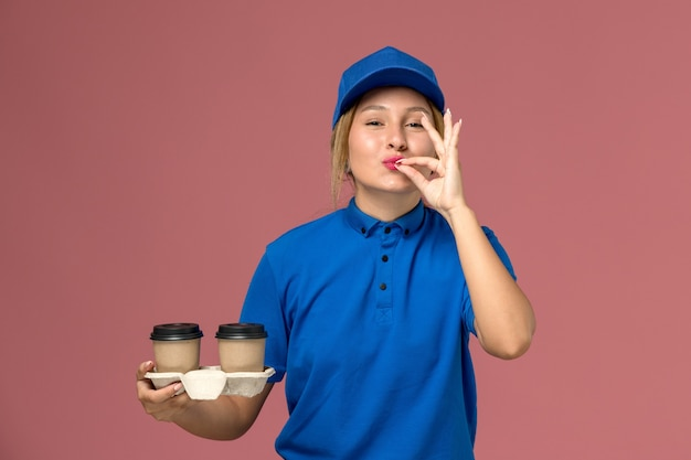 Female courier in blue uniform holding cups of coffee showing tasty sign on pink, service uniform delivery job