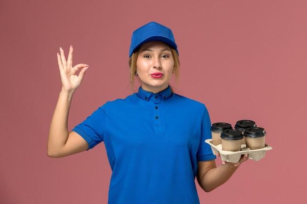Corriere femminile in uniforme blu che tiene le tazze di consegna di caffè in posa sul rosa, consegna uniforme dei lavoratori dei servizi