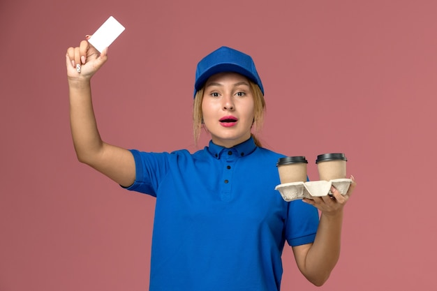 Female courier in blue uniform holding delivery cups of coffee and white card on pink, service uniform delivery job
