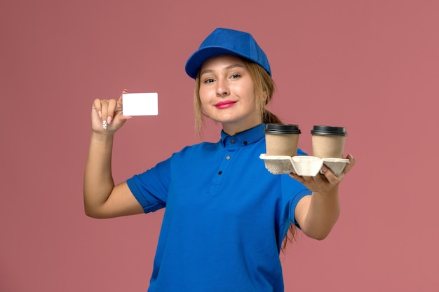 Female courier in blue uniform holding delivery cups of coffee and white card with smile on pink, service uniform delivery