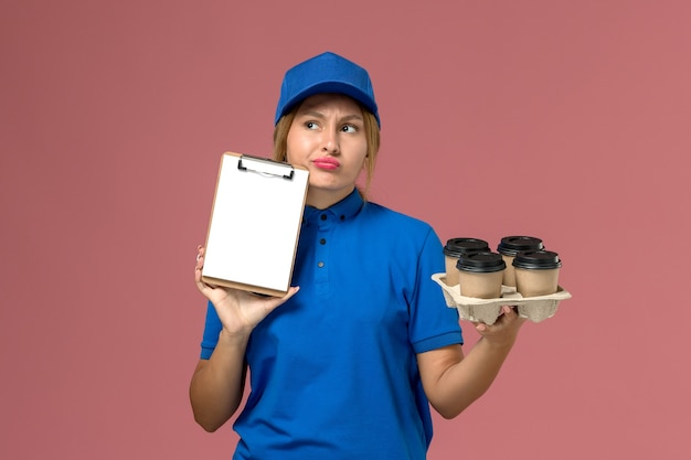 Corriere femminile in uniforme blu che tiene il blocco note insieme a tazze di caffè marroni su consegna uniforme rosa chiaro, servizio di lavoro