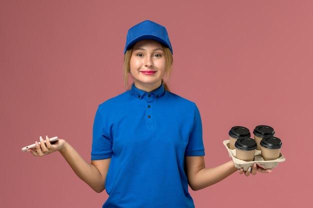 Corriere femminile in uniforme blu che tiene il telefono e con tazze di caffè marroni sul lavoro di consegna dell'uniforme di servizio rosa chiaro