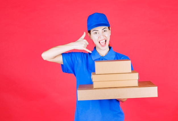 Female courier in blue uniform holding a stock of cardboard boxes and asking for a call.