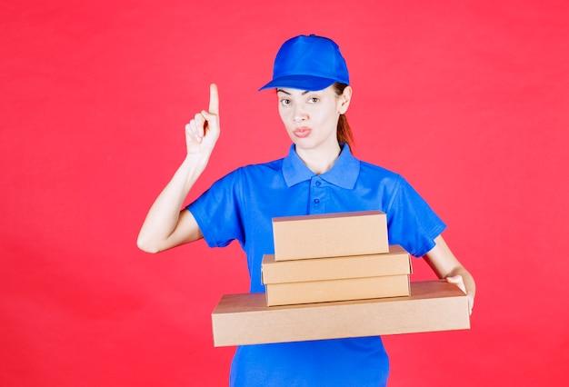 Corriere femminile in uniforme blu che tiene una scorta di scatole di cartone e ha un'idea.