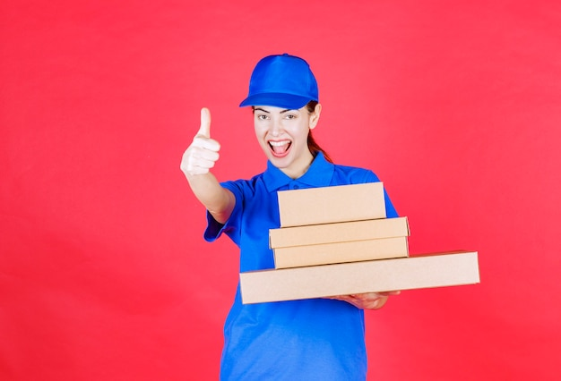 Female courier in blue uniform holding a stock of cardboard boxes and showing enjoyment sign.