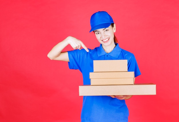 Female courier in blue uniform holding a stock of cardboard boxes .