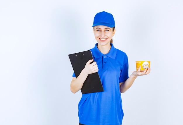 Corriere femminile in uniforme blu che tiene una tazza di noodle da asporto e una cartella nera.