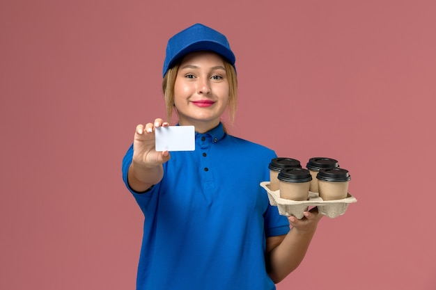 Female courier in blue uniform holding white card along with brown delivery cups of coffee smiling on light-pink, service job uniform delivery