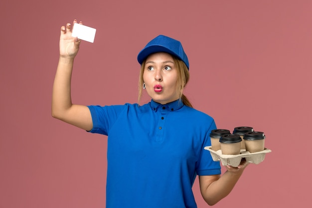Female courier in blue uniform holding white card and brown delivery cups of coffee on light-pink, service job uniform delivery worker