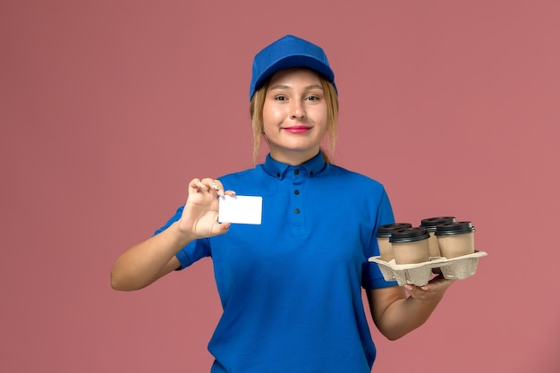 Female courier in blue uniform holding white card and brown delivery cups of coffee on pink, service job uniform delivery worker