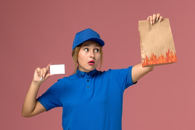 Female courier in blue uniform holding white plastic card and food package on light-pink, service uniform delivery job