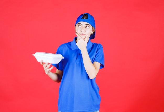 Corriere femminile in uniforme blu che tiene una scatola bianca da asporto e sembra confuso.