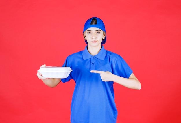 Corriere femminile in uniforme blu che tiene una scatola bianca da asporto.