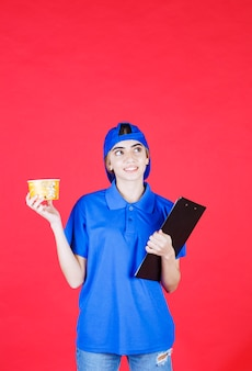 Female courier in blue uniform holding a yellow noodles cup and a black folder.
