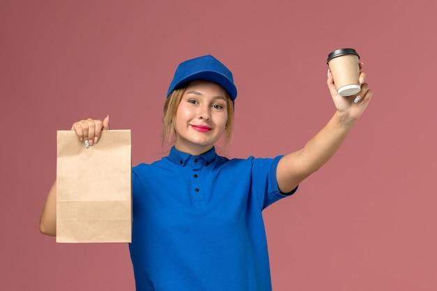 Corriere femminile in uniforme blu in posa tenendo la tazza di caffè e il pacchetto alimentare con il sorriso sul rosa, lavoratore ragazza di consegna uniforme di servizio