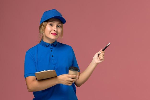 Corriere femminile in uniforme blu che posa tenendo la tazza di caffè e il blocco note sul rosa, foto a colori dell'operaio della ragazza di consegna dell'uniforme di servizio