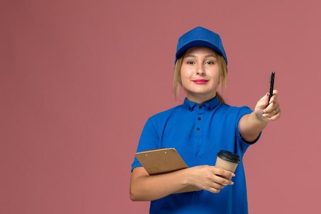 Corriere femminile in uniforme blu che posa tenendo la tazza di caffè e il blocco note con la penna sul rosa, foto a colori dell'operaio della ragazza di consegna dell'uniforme di servizio