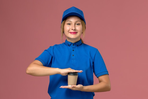 Female courier in blue uniform posing holding cup of coffee with slight smile on pink, service uniform delivery job worker