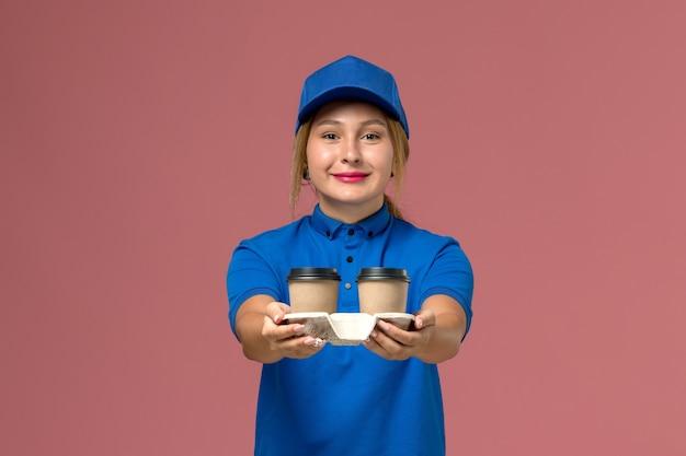 Corriere femminile in uniforme blu in posa e tenendo le tazze di caffè con un leggero sorriso sul rosa, lavoratore di consegna uniforme di servizio