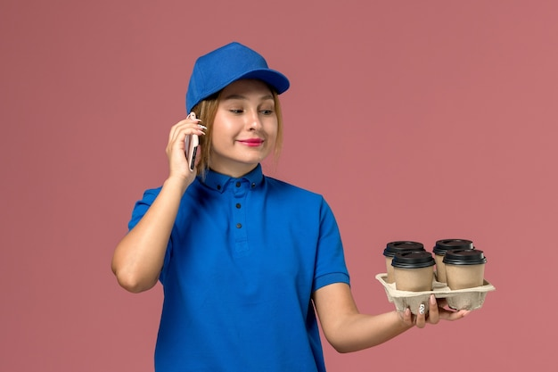 Female courier in blue uniform talking on phone holding brown cups of coffee smiling on light pink, service uniform delivery job