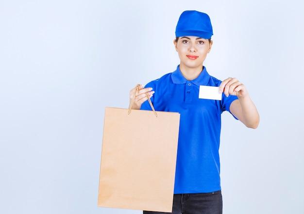 ペーパークラフトバッグを運び、名刺を見せている女性の宅配便。